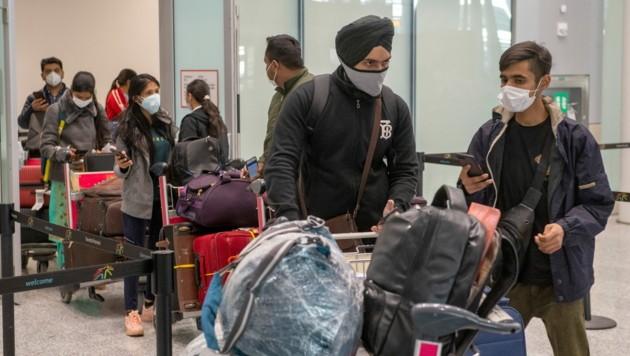 Andere Länder wie Deutschland und Kanada (im Bild Passagiere aus Neu-Delhi am Flughafen Toronto) haben einen Einreisestopp verhängt. (Bild: AP)