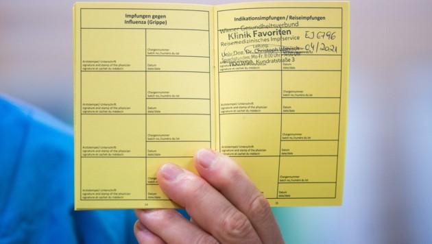 Der gelbe Impfpass soll künftig als Eintrittsberechtigung dienen, etwa für Gastronomie und Hotellerie. (Bild: APA/GEORG HOCHMUTH)