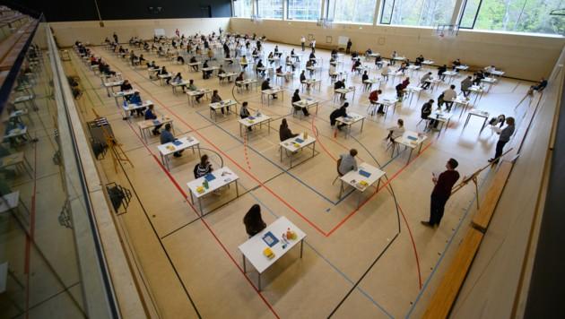 Mit weitem Abstand sitzen Schüler eines deutschen Gymnasiums zur Abiturprüfung an ihren Tischen (Archivbild) (Bild: dpa-Zentralbild/Robert Michael)