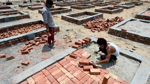 Wegen der rapide steigenden Todeszahlen bauen indische Arbeiter Plattformen zum Kremieren von Covid-19-Toten. (Bild: AFP)