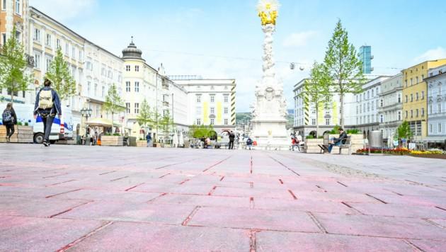 """Der """"rote Platz"""" von Linz - nach einer PR-Aktion der SPÖ am 1. Mai geht die Farbe nicht mehr ab. Die städtischen Hauptplatzreiniger kümmern sich nun darum. (Bild: Alexander Schwarzl)"""