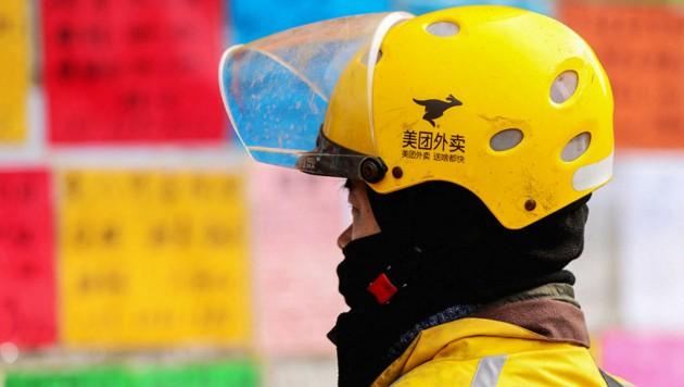 Ein Lieferant des chinesischen Online-Zustellers Meituan (Bild: APA/AFP/STR)