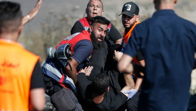 Palästinensische Rettungskräfte transportieren einen verletzten Demonstranten ab. Am Dienstag gab es wieder Zusammenstöße in Gaza und Ost-Jerusalem. (Bild: AFP)