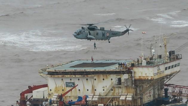 Ein Helikopter rettet Menschen von einem Lastkahn vor der Küste Indiens. (Bild: APA/AFP/INDIAN NAVY)