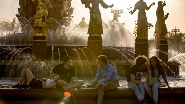 Diese jungen Russen genießen die ungewöhnlich warme Abendsonne in Moskau. (Bild: Associated Press)