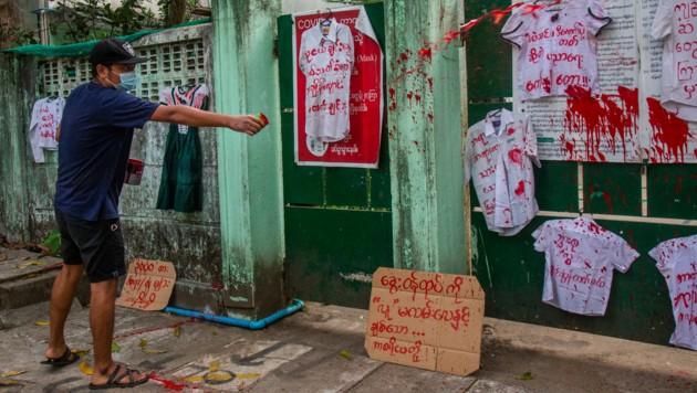 Demo gegen das Militärregime in Myanmar vor einer Schule. Ein Demonstrant versprüht rote Farbe auf Schuluniformen. (Bild: The Associated Press)
