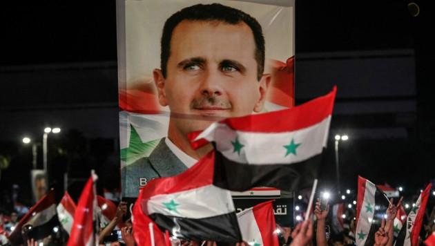 Fans von Syriens Präsident Bashar al-Assad feiern dessen Wahlsieg. (Bild: AFP)