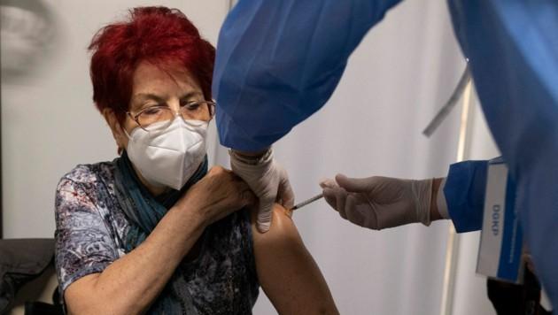 Verabreichung einer Spritze in der Impfstraße im Wiener Austria Center (Bild: APA/AFP/JOE KLAMAR)