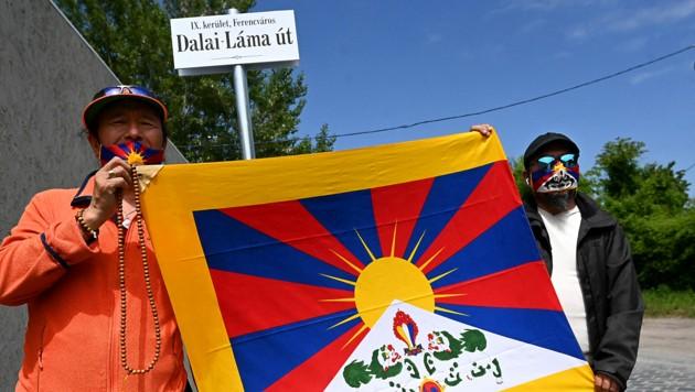 Aktivisten mit der tibetischen Flagge vor dem Schild der Dalai-Lama-Straße in Budapest (Bild: APA/AFP/Attila KISBENEDEK)