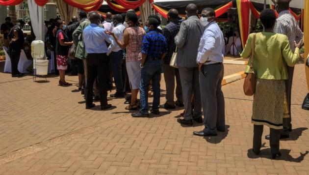 Menschen warten in Kampala, der Hauptstadt Ugandas, auf eine Covid-Impfung (Bild: AFP)