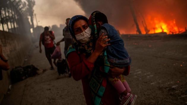 Aus dem brennenden Lager flüchtende Asylwerber im September 2020 (Bild: APA/AFP/ANGELOS TZORTZINIS)