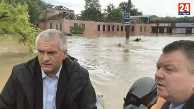 Sergej Aksjonow (links) sitzt im Boot, die Leibwächter schwimmen hinterdrein. (Bild: twitter.com/Screenshot)