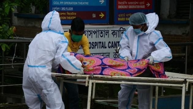 In Sicherheitsmontur bringen diese Spitalsangestellten in Indien einen an Covid-19 verstorbenen Patienten weg. (Bild: AFP)