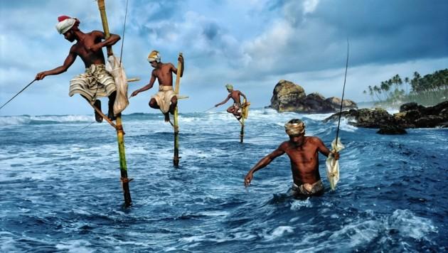 Fischer in Weligama in Sri Lanka werfen auf traditionelle Weise ihre Leinen aus (entstanden 1995). (Bild: galeriejungwirth.com/Steve McCurry)
