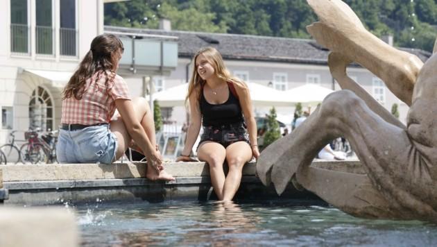 Zwei junge Frauen suchen Abkühlung im Residenzbrunnen. (Bild: Tschepp Markus)