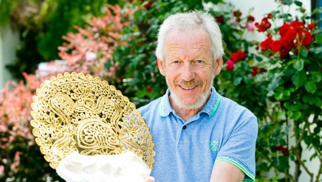 Michael Selb und eine seiner selbstgefertigten Goldradhauben - ein Meisterwerk (Bild: Mathis Fotografie)