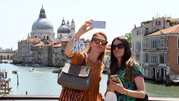 Touristinnen genießen eine Tour durch Venedig (Bild: AFP )