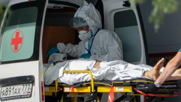 Sanitäter versorgen einen vermutlich mit dem Coronavirus infizierten Patienten. (Bild: AP)
