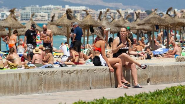 Touristen am Strand von Palma de Mallorca im Juni 2021 (Bild: AFP)