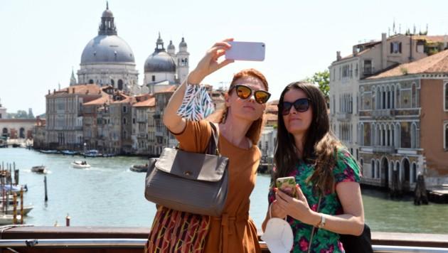 Die Maske darf in Italien nun getrost im Freien am Handgelenk baumeln. (Bild: AFP)