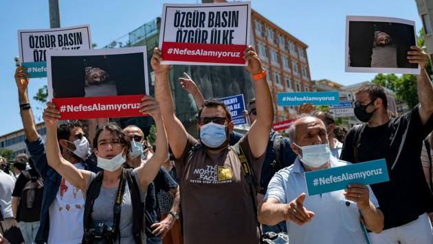 """Journalistenkollegen protestieren gegen die Verhaftung mit Transparenten, die die Aufschrift tragen: """"Wir können nicht atmen."""" (Bild: APA/AFP/Yasin AKGUL)"""