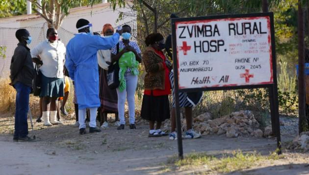 Ein Mitarbeiter eines ländlichen Krankenhauses in Zimbabwe misst die Temperatur von möglichen Corona-Patienten. (Bild: AP)