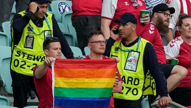 Ordner nähern sich zwei dänischen Fans mit Regenbogenflagge. (Bild: AP)