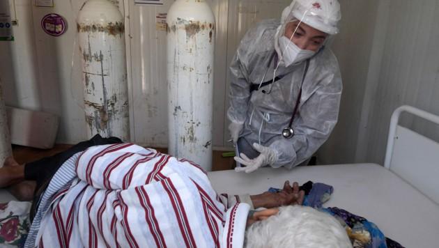 Eine Krankenschwester kümmert sich um einen Patienten. (Bild: AFP)