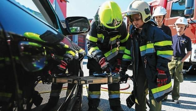 Beim Zerschneiden des Unfallfahrzeuges mit dem hydraulischen Rettungsgerät waren die jungen Feuerwehrmänner eifrig dabei. (Bild: CHRISTIAN IRRASCH)