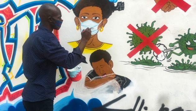Der kongolesische Künstler Chris Shongo bemalt wie Außenwand der Kunstakademie in Kinshasa. (Bild: AFP)