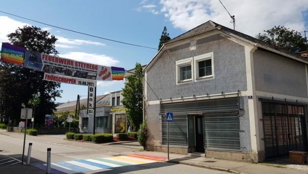 Die rechtsextreme Identitäre Bewegung baut in Steyregg bei Linz eine neue Basis auf. Die Gemeinde ist damit nicht glücklich und wehrt sich nun mit einem bunten Zeichen: Vor dem neuen Identitären-StŸützpunkt wurde am Donnerstag ein Schutzweg in den Farben des Regenbogens aufgemalt. (Bild: APA/JOHANN WÜRZBURGER)