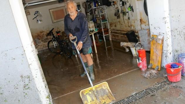 Rudolf Ladinek beseitigt die Spuren der Nacht: Mehr als einen Meter hoch stand das Wasser in seiner Garage. (Bild: Christian Jauschowetz)