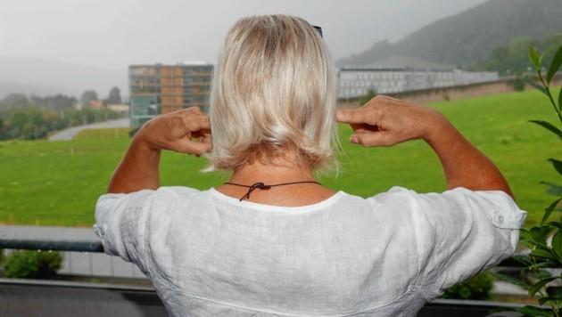 Irmgard Zenz (57) findet auch auf ihrem Balkon keine Ruhe - zu laut ist das Gegröle aus der benachbarten Justizanstalt. (Bild: Erwin Scheriau / KRONE)