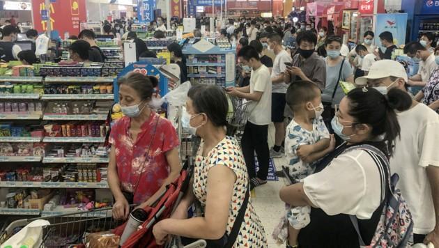 Menschen drängen sich in einem Supermarkt in Wuhan. In anderen chinesischen Städten wurden aus Angst vor der Delta-Variante bereits Lockdowns verhängt. (Bild: APA/AFP/STR)
