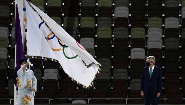 Tokyo-Bürgermeisterin Yuriko Koike (L) mit der Flagge, vorne spricht IOC-Präsident Thomas Bach. (Bild: AFP)