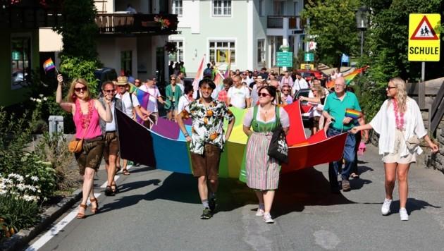 Sie spazierten am Samstag mit einer 12 Meter langen Regenbogenfahne durch den Ort. (Bild: Roland Hölzl)
