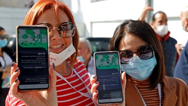 Zwei Konzertbesucherinnen weisen in einem Stadion in Tel Aviv ihren Grünen Pass vor. (Bild: APA/AFP/JACK GUEZ)