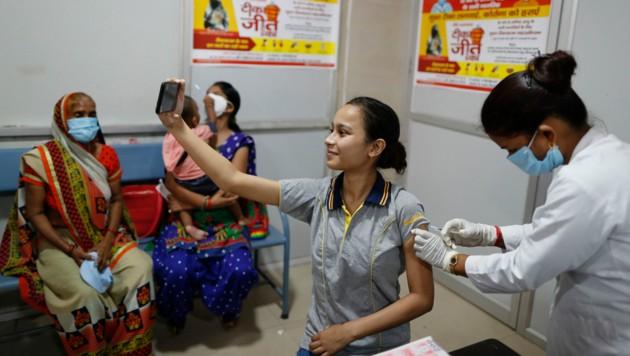 Eine Inderin hält den Moment ihrer Impfung mit einem Selfie fest. (Bild: Associated Press)