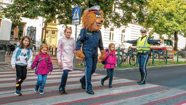 Das Polizeimaskottchen begleitet die Kinder über die Straße. (Bild: LPD Wien)