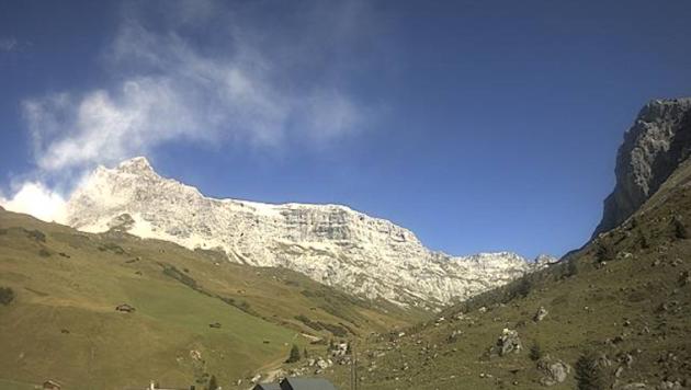 """Was auf den ersten Blick wie eine """"normale"""" Wolke unterhalb des Sulzfluh-Gipfels aussieht, ist in Wahrheit jene Staubwolke, die der gewaltige Felssturz an der Südwand des 2818 Meter hohen Berges auslöste. (Bild: Screenshot Webcam St. Antönien)"""