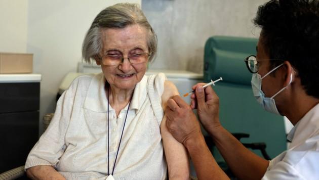Diese ältere Französin bekommt ihren dritten Stich verpasst. (Bild: AFP)