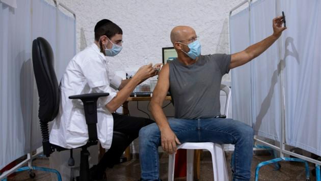 Selfie bei der Booster-Impfung: Ein Mann erhält in Israel die dritte Dosis Pfizer-Vakzin. (Bild: AP)