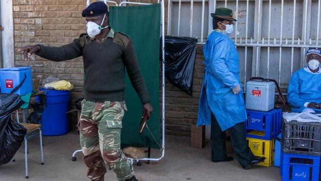 Ein Soldat kontrolliert die Warteschlange vor einer Impfstation in der Stadt Bulawayo. (Bild: APA/AFP/Zinyange Auntony)
