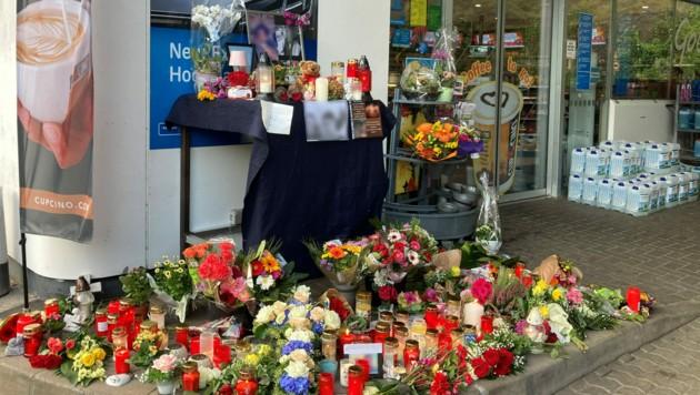 Blumen und Kerzen sind vor jener Tankstelle in Idar-Oberstein aufgestellt, in der ein 20 Jahre alter Mitarbeiter erschossen wurde, weil er auf die Einhaltung der Corona-Maßnahmen hingewiesen hatte. (Bild: APA/dpa/Birgit Reichert)