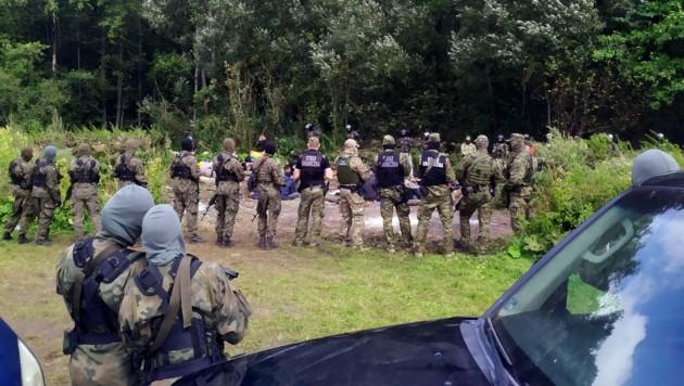 Migranten werden von der polnischen Polizei festgehalten, nachdem sie von Weißrussland aus die Grenze überquert haben. (Bild: The Associated Press)