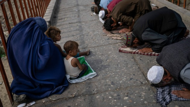 Eine Frau in Burka und zwei Kinder betteln auf den Straßen Kabuls während des Freitagsgebets. (Bild: AP)