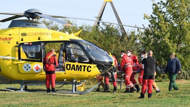 Lebensrettung ist Teamarbeit: Mit vereinten Kräften wird der Patient zum Helikopter getragen. (Bild: P. Huber)