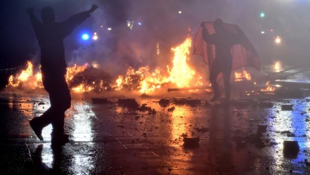 Vermummte Randalierer legten Feuer und gingen ohne Skrupel gegen Polizisten vor. (Bild: AFP)