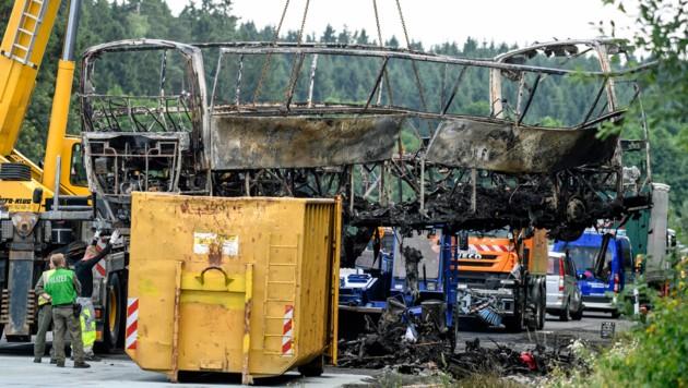 Die komplett ausgebrannten Überreste des Busses werden mit einem Kran geborgen. (Bild: ASSOCIATED PRESS)