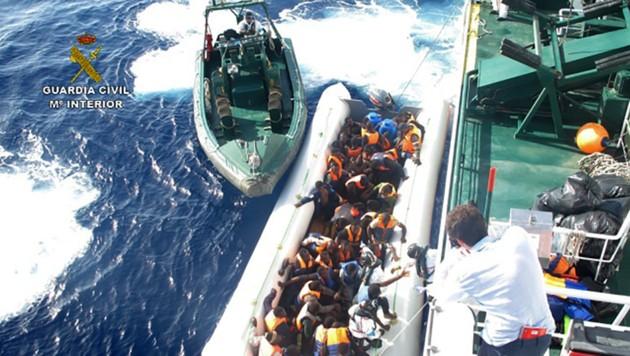 Die spanische Küstenwache bei der Rettung von Flüchtlingen vor der Küste Libyens (Bild: AFP)